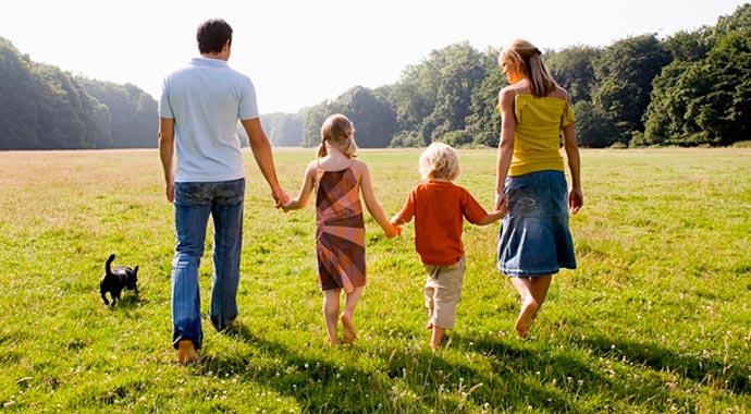 Une famille de 4 et leurs chiens se baladent dans un champ en se tenant la main.