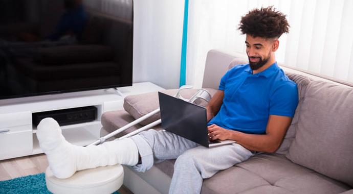 Un jeune homme avec la jambe dans le plâtre consulte nos dispositifs sur le site Lourmel.