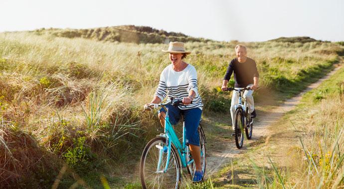 Homme et femme retraités se baladant joyeusement à vélo dans la nature