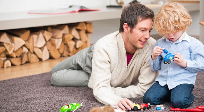 un homme allongé sur un tapis joue avec son enfant avec des voiturettes