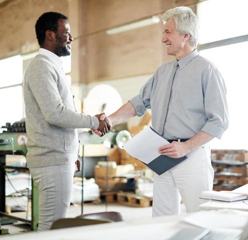 Un patron félicite son employé en lui serrant la main.