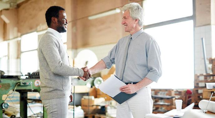 Un patron félicite son employé en lui serrant la main