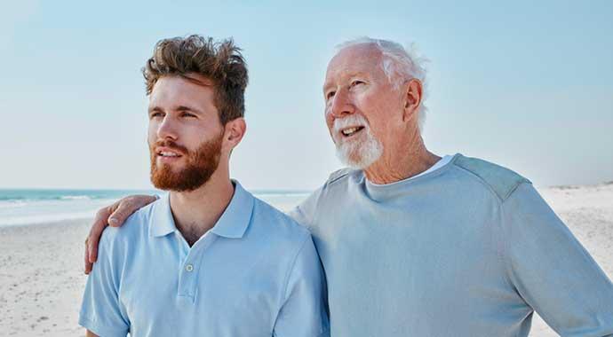 Une jeune homme et son grand père se promènent sur la plage.