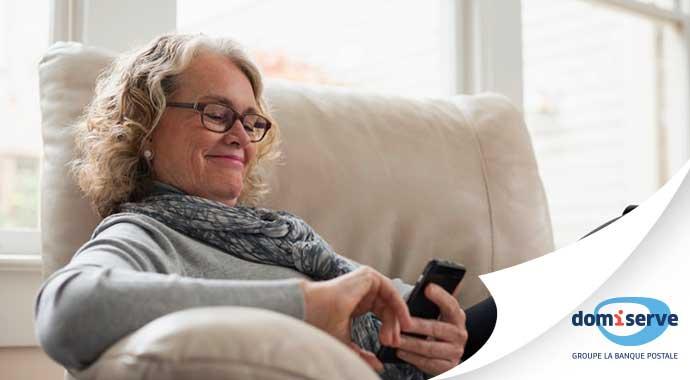 Femme retraitée consultant son smartphone avec Sérénité service à domicile de notre partenaire Domiserve