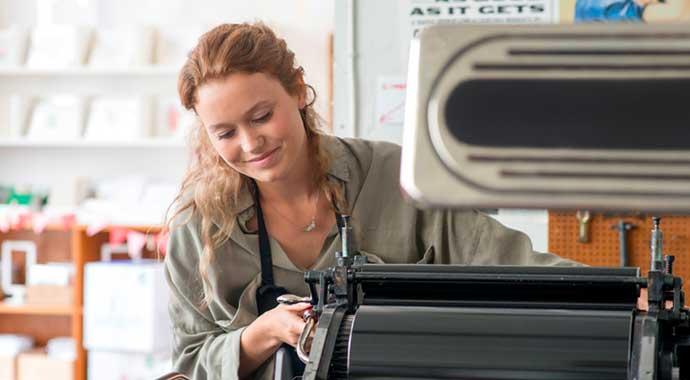 Une femme réglant une machine d'impression dans son atelier