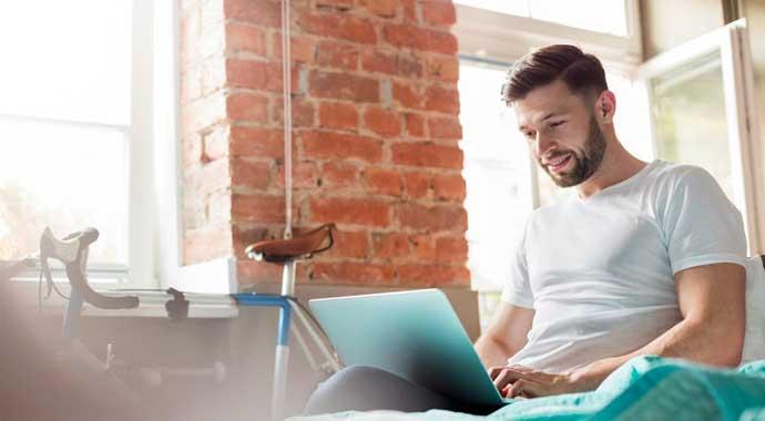 Un jeune homme consulte le site Lourmel sur son ordinateur portable