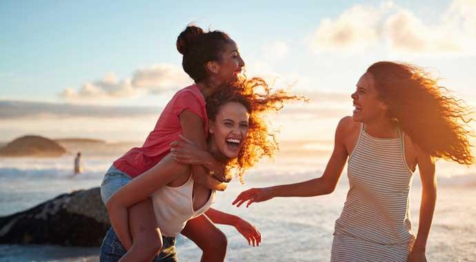 Trois jeunes filles s'amusent sur la plage au soleil couchant.
