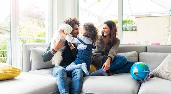 Famille avec un chien s'amusant sur un canapé en bonne santé