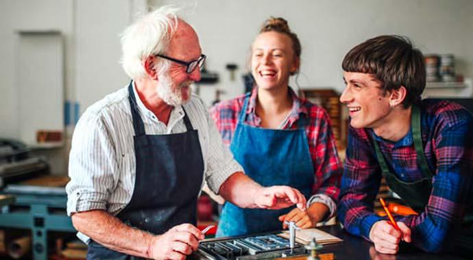 Trois imprimeurs travaillent dans la bonne humeur, sereinement grâce à la protection sociale  de Lourmel