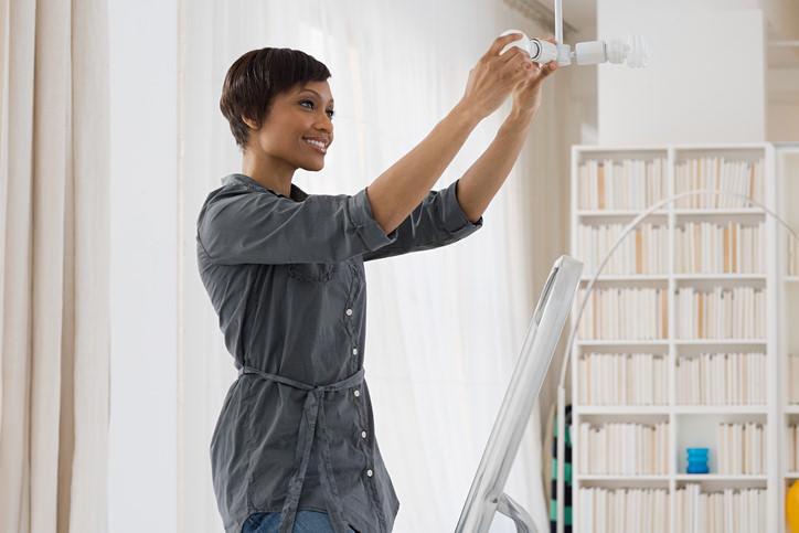 Une femme sur un escabeau change son ampoule LED.