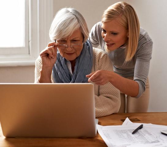 Une personne agée assistée par une femme lors de l'utilisation d'un ordinateur