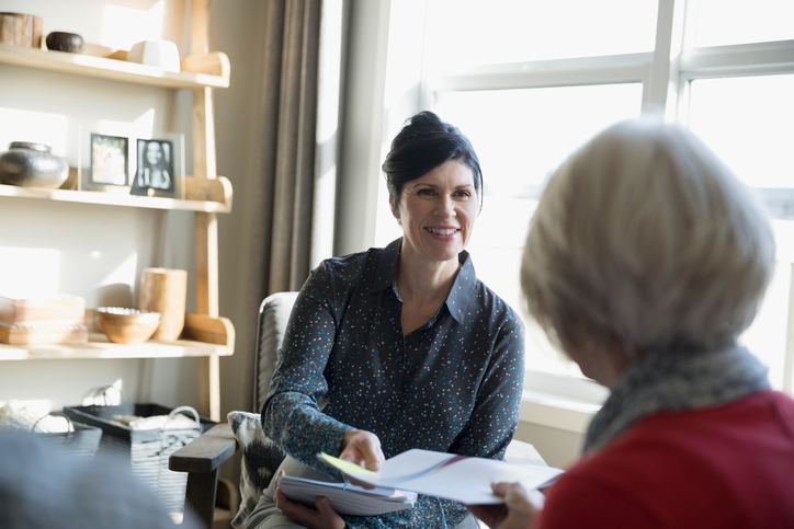 Femme tendant un contrat à une retraitée