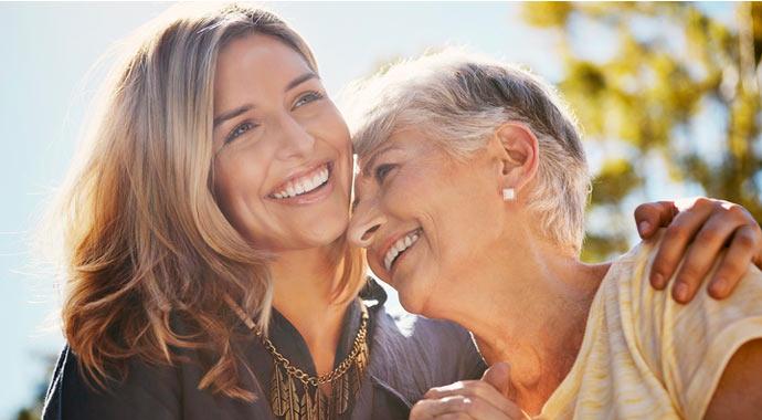Une femme et sa mère s'enlace et rient aux éclats.