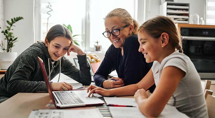 une femme aide des enfants à faire leurs devoirs dans la bonne humeur.
