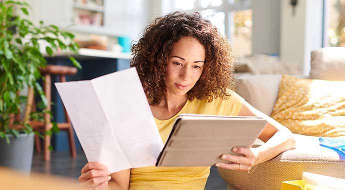 une femme consulte sa feuille d'imposition et fait une comparaison avec sa tablette