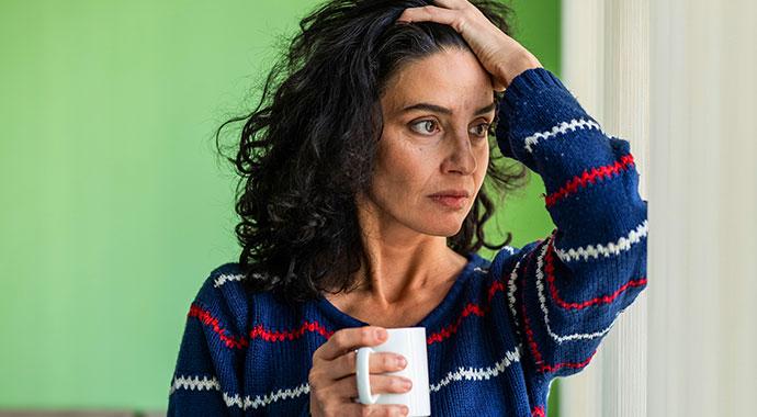 Une femme en proie a des doutes se passe la main dans ses cheveux