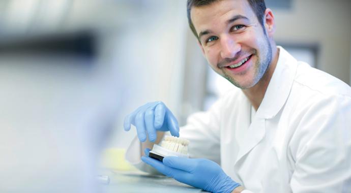 Dentiste manipulant un prothèse dentaire