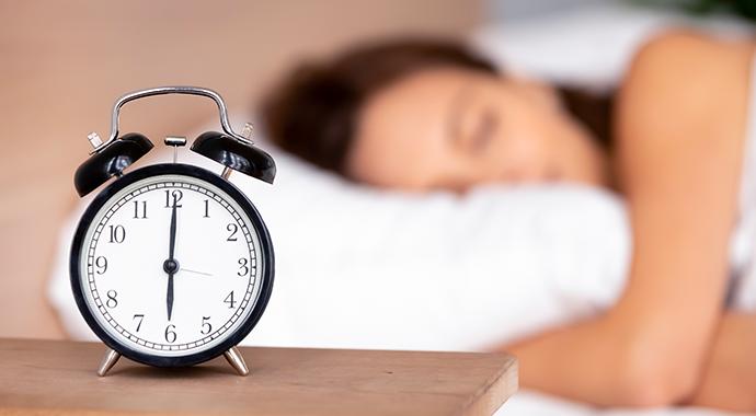 Réveil et personne en sommeil en fond floutée
